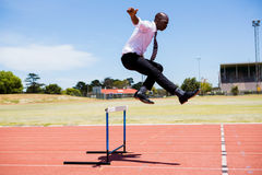 Businessman jumping a hurdle while running Royalty Free Stock Images