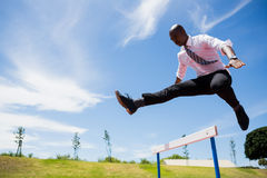 Businessman jumping a hurdle while running Royalty Free Stock Photos