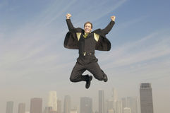 Businessman Jumping In Joy Above City. Full length of young businessman jumping in joy above city Stock Photography
