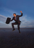 Businessman jumping for joy on beach Stock Photos