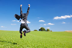 Businessman jumping for joy. Celebrating a successful achievement in a lush green field under a blue sky Royalty Free Stock Image