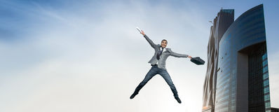Businessman jumping in joy. Full length of smart happy man holding briefcase in the air. outdoors Royalty Free Stock Photo