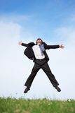 Businessman jumping on the meadow royalty free stock photo