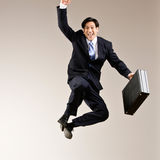 Businessman jumping in mid-air cheering. Excited businessman jumping in mid-air cheering and celebrating his success Stock Photo