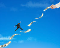 Businessman jumping on money with hand hold one. In blue sky background stock photography