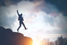 Businessman jumping in a morning city. Silhouette of a young businessman jumping on a rock against a big city sky background. Concept of business success. Toned stock illustration