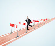Businessman jumping over barrier Stock Photos
