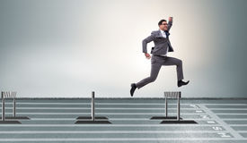 The businessman jumping over barriers in business concept Stock Photo