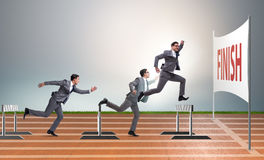 The businessman jumping over barriers in business concept Stock Images