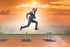 The businessman jumping over barriers in business concept Royalty Free Stock Image