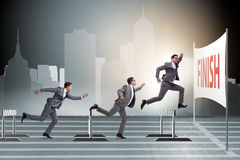 The businessman jumping over barriers in business concept Stock Image