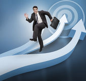Businessman jumping over blue arrows Royalty Free Stock Photos