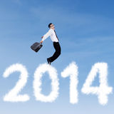 Businessman jumping over clouds of 2014 Royalty Free Stock Images