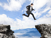 Businessman jumping over danger precipice. On the mountain, concept for business, asian people royalty free stock images