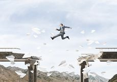 Problems and difficulties overcoming concept. Businessman jumping over gap in bridge among flying paper planes as symbol of overcoming challenges. Skyscape and Royalty Free Stock Photo