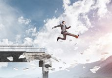 Problems and difficulties overcoming concept. Businessman jumping over gap in bridge among flying paper planes as symbol of overcoming challenges. Skyscape with Stock Photography