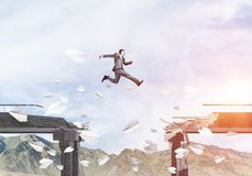Problems and difficulties overcoming concept. Businessman jumping over gap in bridge among flying paper planes as symbol of overcoming challenges. Skyscape with Royalty Free Stock Images