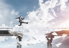 Problems and difficulties overcoming concept. Businessman jumping over gap in bridge among flying paper planes as symbol of overcoming challenges. Skyscape with Royalty Free Stock Photography