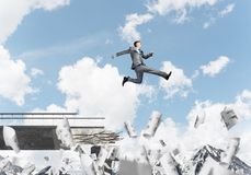 Problems and difficulties overcoming concept. Businessman jumping over gap in bridge among flying papers as symbol of overcoming challenges. Skyscape and nature Royalty Free Stock Photo