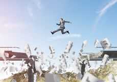 Problems and difficulties overcoming concept. Businessman jumping over gap in bridge among flying papers as symbol of overcoming challenges. Skyscape with Royalty Free Stock Photos