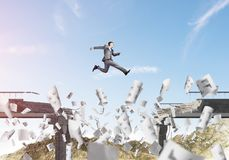Problems and difficulties overcoming concept. Businessman jumping over gap in bridge among flying papers as symbol of overcoming challenges. Skyscape with Stock Images