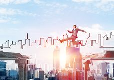 Problem and difficulties overcoming concept. Businessman jumping over gap in concrete bridge as symbol of overcoming challenges. Sunlight and cityscape on Royalty Free Stock Photos