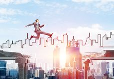 Problem and difficulties overcoming concept. Businessman jumping over gap in concrete bridge as symbol of overcoming challenges. Sunlight and cityscape on Stock Images