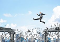 Problem and difficulties overcoming concept. Businessman jumping over gap with flying letters in concrete bridge as symbol of overcoming challenges. Cityscape Stock Photo