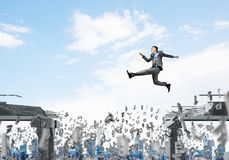 Problem and difficulties overcoming concept. Businessman jumping over gap with flying letters in concrete bridge as symbol of overcoming challenges. Cityscape Stock Photography