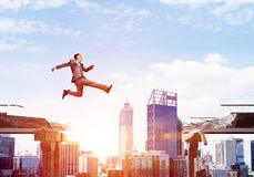 Problem and difficulties overcoming concept. Businessman jumping over gap with flying letters in concrete bridge as symbol of overcoming challenges. Cityscape Royalty Free Stock Photography