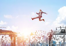 Problem and difficulties overcoming concept. Businessman jumping over gap with flying letters in concrete bridge as symbol of overcoming challenges. Cityscape Royalty Free Stock Images