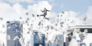 Problem and difficulties overcoming concept. Businessman jumping over gap with flying paper documents in concrete bridge as symbol of overcoming challenges Royalty Free Stock Image