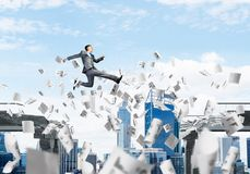 Problem and difficulties overcoming concept. Businessman jumping over gap with flying paper documents in concrete bridge as symbol of overcoming challenges Royalty Free Stock Photo