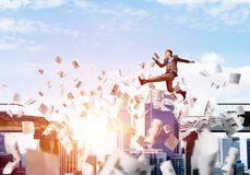 Problem and difficulties overcoming concept. Businessman jumping over gap with flying paper documents in concrete bridge as symbol of overcoming challenges Royalty Free Stock Photography