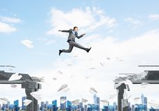 Problem and difficulties overcoming concept. Businessman jumping over gap with flying paper planes in concrete bridge as symbol of overcoming challenges Stock Photography