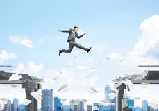 Problem and difficulties overcoming concept. Businessman jumping over gap with flying paper planes in concrete bridge as symbol of overcoming challenges Royalty Free Stock Image