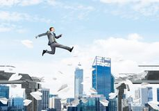 Problem and difficulties overcoming concept. Businessman jumping over gap with flying paper planes in concrete bridge as symbol of overcoming challenges Royalty Free Stock Photography