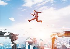 Problem and difficulties overcoming concept. Businessman jumping over gap with flying paper planes in concrete bridge as symbol of overcoming challenges Royalty Free Stock Photos