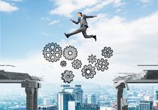 Problem and difficulties overcoming concept. Businessman jumping over gap with gear mechanism in concrete bridge as symbol of overcoming challenges. Cityscape Royalty Free Stock Images