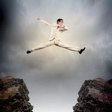 Businessman jumping over gap. Image of young businessman jumping over gap Stock Photo