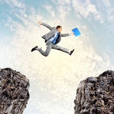 Businessman jumping over gap. Image of young businessman jumping over gap Royalty Free Stock Image