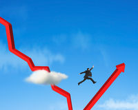 Businessman jumping over gowing down red arrow Stock Image