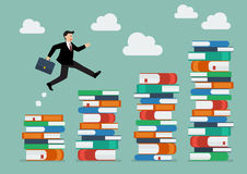 Businessman jumping over higher stack of books Stock Photo