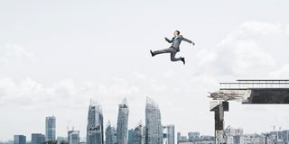 Problem and difficulties overcoming concept. Businessman jumping over huge gap in concrete bridge as symbol of overcoming challenges. Cityscape on background Stock Photos