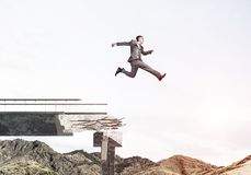 Problems and difficulties overcoming concept. Businessman jumping over huge gap in concrete bridge as symbol of overcoming challenges. Skyscape and nature view Royalty Free Stock Images