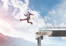 Problems and difficulties overcoming concept. Businessman jumping over huge gap in concrete bridge as symbol of overcoming challenges. Skyscape and nature view Stock Images