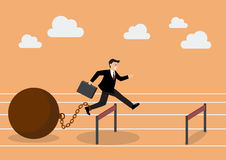Businessman jumping over hurdle with the weight Stock Photo