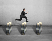 Businessman jumping over money symbols Royalty Free Stock Images