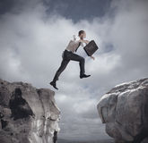 Businessman jumping over the mountains Stock Image