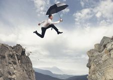 Businessman jumping over the mountains stock photo